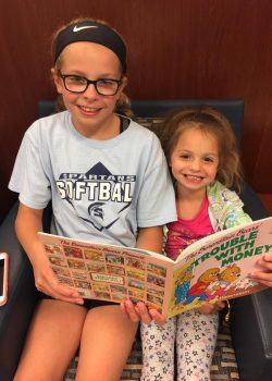 Sisters Claire and Erin check out the math and money reading library and Catholic Vantage Financial.