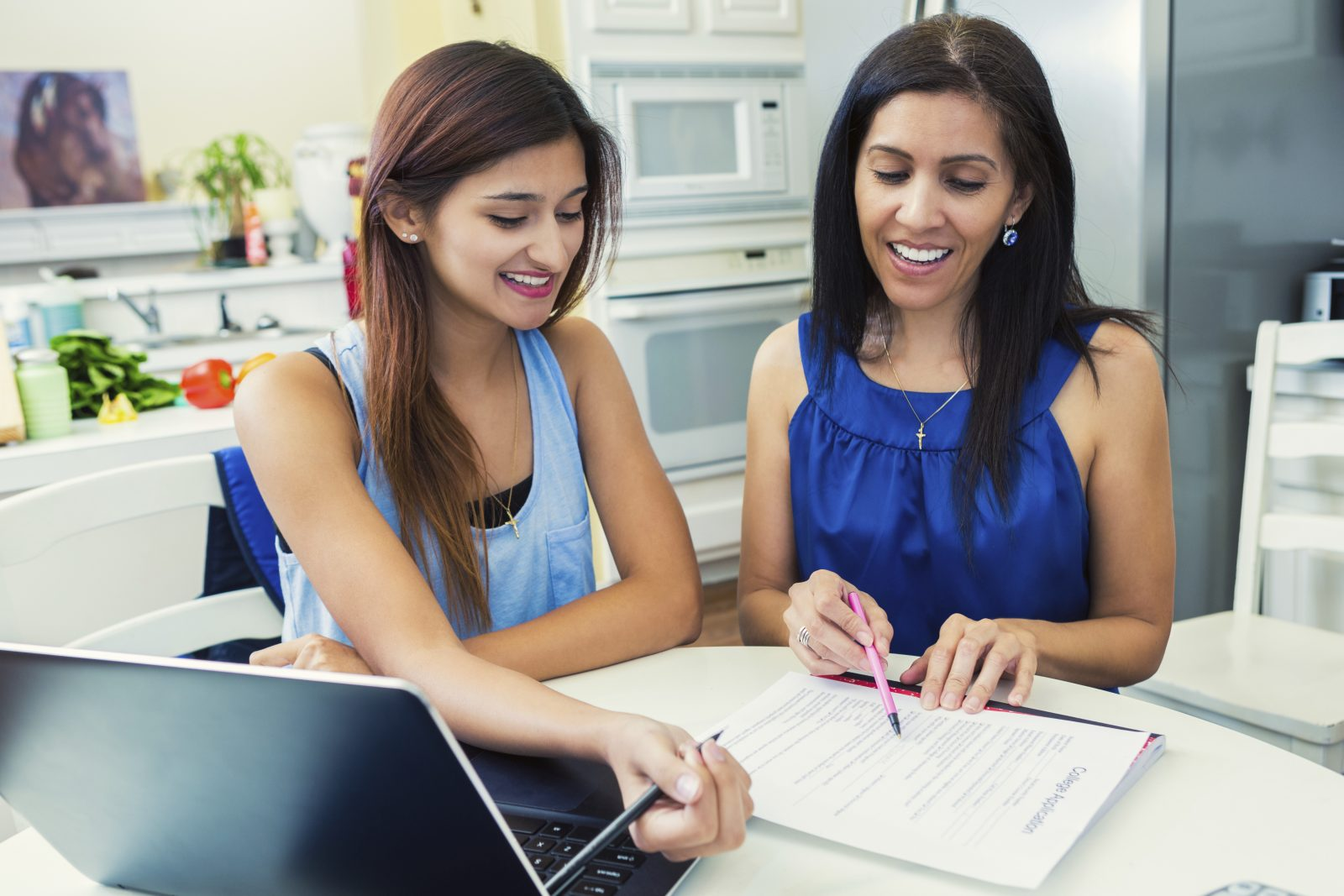 Mother helping daughter fill out College Applications in the Kitchen