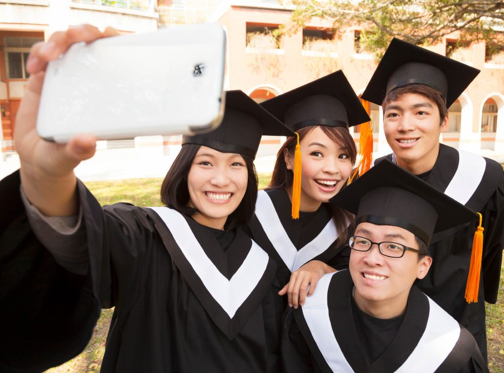 group of graduates taking picture with cell phone