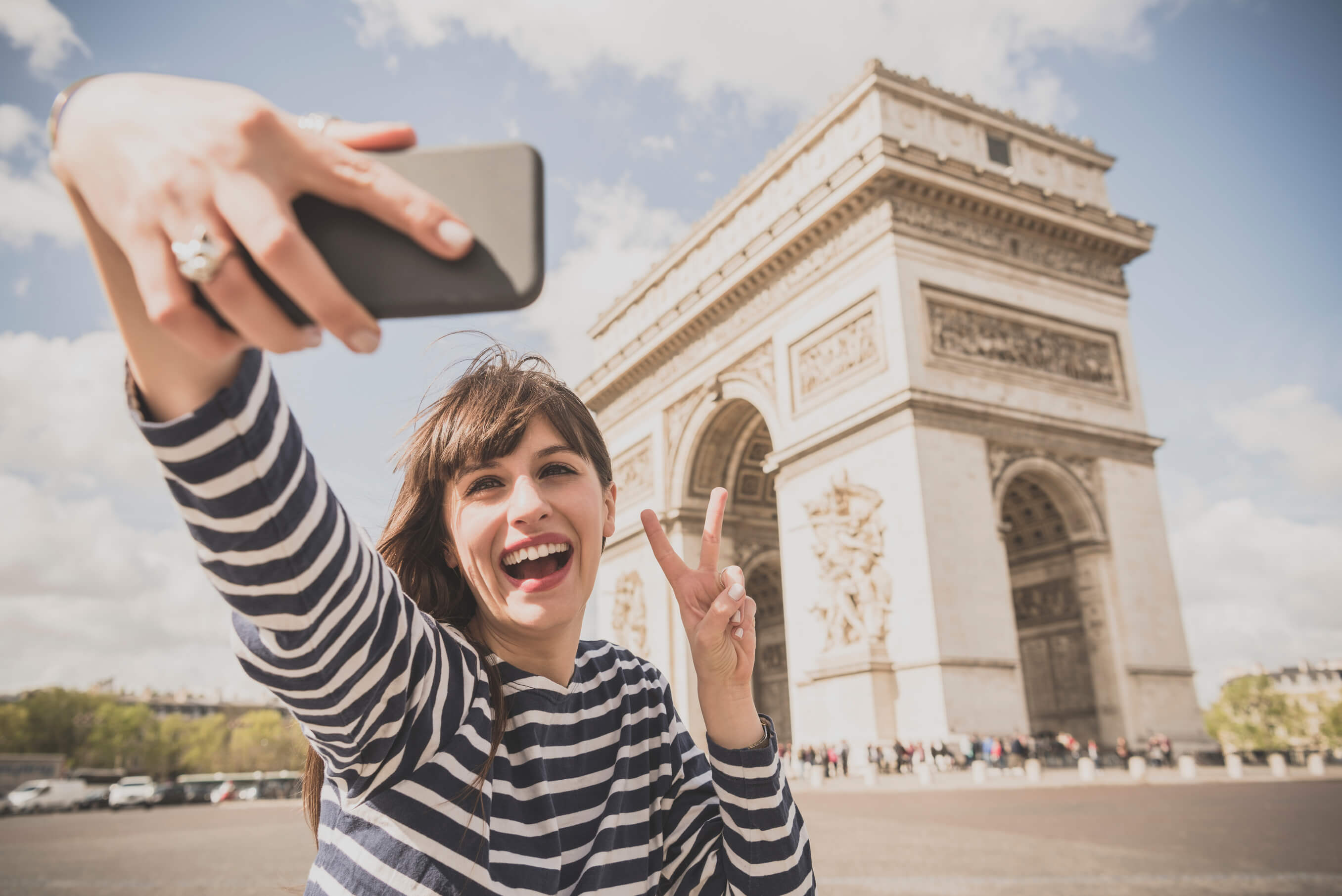 Woman having fun taking photo of herself by landmark in Paris, France. Young woman with camera phone posing for selfie